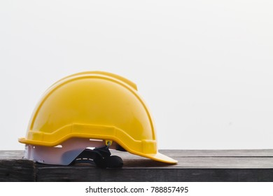 Yellow helmets were prepared for workers to wear before entering the construction area to prevent the danger of falling objects from working. Yellow safety helmet is placed on a wooden table.