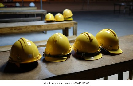 Yellow helmets of worker and engineer put on the wood table in construction site