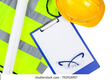 Yellow hi vis safety vest and hard hat with glasses and a clipboard with copyspace