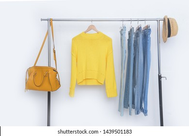yellow hoodie sweater with blue jeans on hanger with yellow handbag, hat