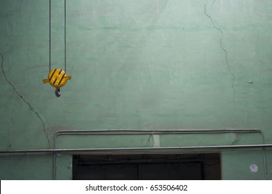 Yellow hook of the crane against the background of the old green and cracked wall