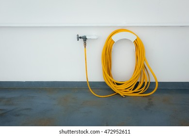 Yellow hose coiled by white wall