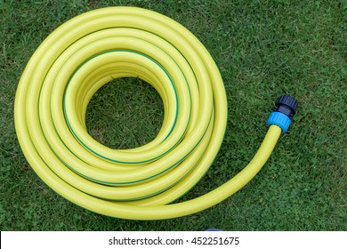 Yellow hose-pipe in a green grass