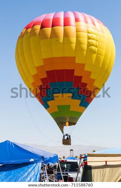 Yellow Hot Air Balloon Above Car Stock Photo (Edit Now