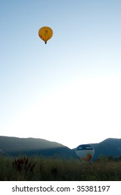 Yellow hot air balloon floating far above mountains in evening.