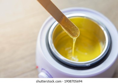 Yellow hot liquid wax for depilation on a wooden stick. The concept of depilation, beauty, skin care.