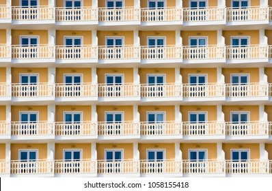 Yellow hotel exterior with small balconies and windows tourism background, Spain.