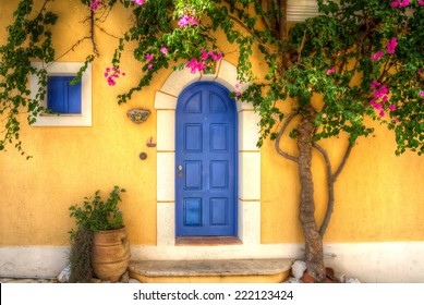 Yellow house with Blue Door in the village of Asos, Kefalonia, Greece.