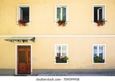 A yellow house facade with open and closed windows with flowers and a wood frontal door.