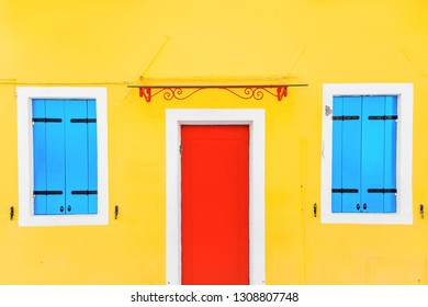 Yellow house with red Door in the village of Burano, Venice