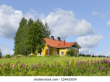 Yellow house with a red roof on the hill. Finland