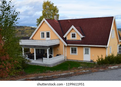 Yellow house with white wooden fence and red roof tiles - Kongsvinger, Norway