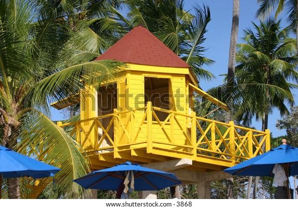 yellow hut beneath palm trees