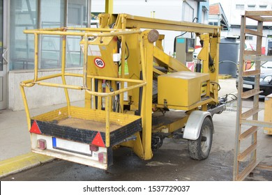 Yellow hydraulic lift, telehandler used for lifting workers, parked at the gas station.