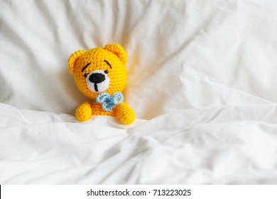 Yellow ill teddy bear lying in bed on white background. Ill or lazy concept.