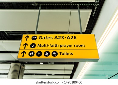 Yellow illuminated airport sign pointing the direction for gates, toilets and multi-faith prayer room