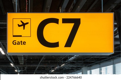 Yellow illuminated sign at airport with gate number for departing flights