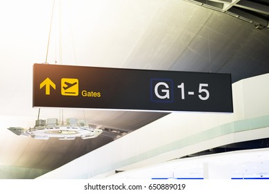 Yellow illuminated sign at airport with gate arrow for departing flights