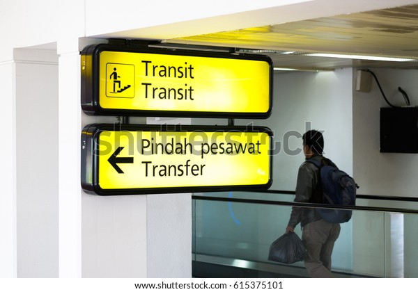Yellow illuminated sign at airport with Transit and Tranfer  information board sign