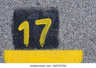 Yellow imprint of the number seventeen on a tarmac street.