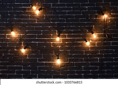 a lot of yellow incandescent light bulbs hang on the background of a black brick wall