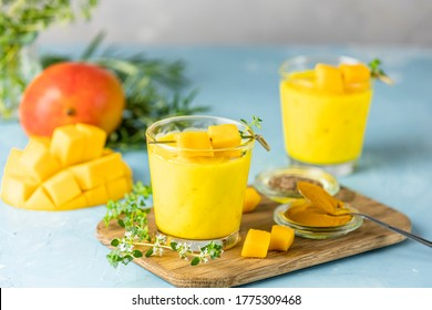 Yellow Indian mango yogurt drink Mango Lassi or smoothie with turmeric and saffron. Healthy probiotic Indian cold summer drink on blue background.