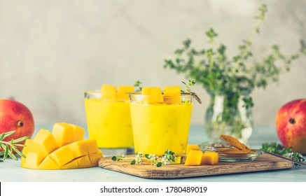 Yellow Indian mango yogurt drink Mango Lassi or smoothie with turmeric and saffron. Healthy probiotic Indian cold summer drink on blue background
