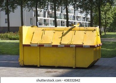 Yellow industrial garbage skip in a street in Rotterdam in the Netherlands