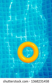 yellow Inflatable ring floating in swimming pool on sunny day, top view