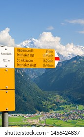 Yellow information sign on top of Harder Kulm, Interlaken, Switzerland. The tourist sign specifies the distances and directions. Beautiful summer Alpine landscape in background. Swiss Alps, tourism