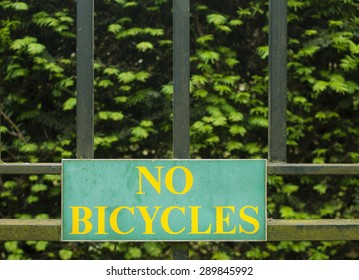 Yellow inscription No Bicycles on teal Sign on black fence and green background