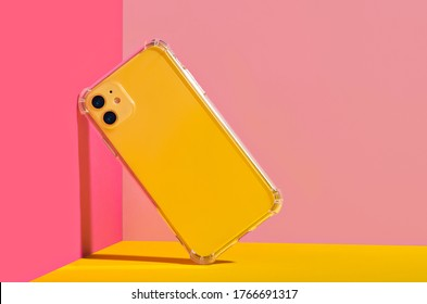 Yellow iPhone 11 in clear phone case, bright and colorful phone case mock up