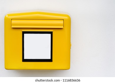 Yellow iron mailbox on white wall. Close-up photo of mail box with empty sign in Germany, Europe