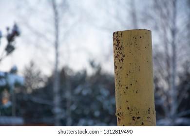 Yellow iron pillar. Winter season, snow on trees.