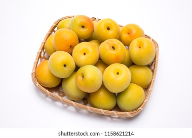 Yellow japanese apricot fruit on a bamboo sieve in front of white background