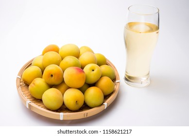 Yellow japanese apricot fruit on a bamboo sieve in front of ume liquor with glass