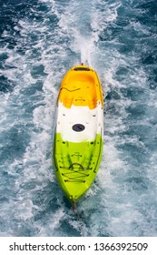 Yellow kayak boat tied with rope and pulled by big boat in sea.