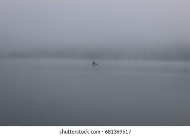 Yellow kayak in the early morning fog