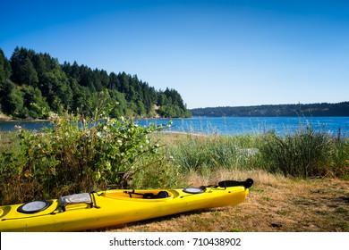 Yellow kayak on a grassy beach next to the water. Location: Vashon Island near Seattle