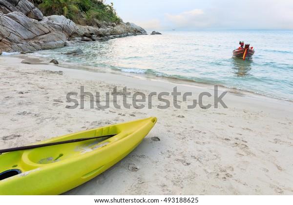 yellow kayak on white sand of tropical sunset beach