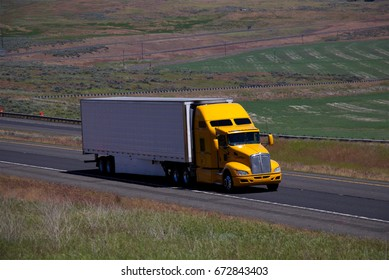 A Yellow Kenworth Semi-Truck Pulling a white unmarked trailer along a rural Oregon Highway.  June 20th, 2017 Rural Oregon, USA