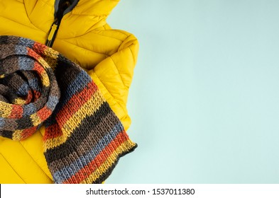 Yellow kids winter jacket composition on blue background. Flat lay, layout and tabletop mockup with copy space.