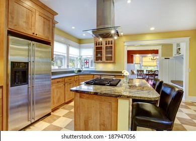 Yellow kitchen interior. View of island with built-in stove and kitchen hood above it