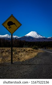 Yellow Kiwi bird crossing warning sign on road side in front of snow capped Mount Ruapehu