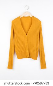 Yellow knitted cardigan hanging on a hanger