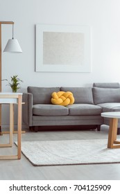 Yellow knot pillow on grey sofa in cozy living room with white carpet on floor and simple painting on wall