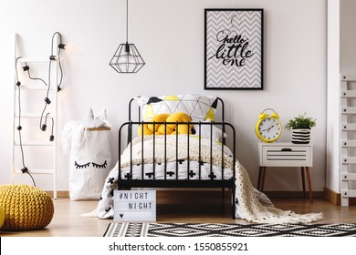 Yellow knot pillow on single metal bed in bright bedroom interior with white scandinavian ladder, paper bag with toys and nightstand with yellow clock and green plant in striped pot
