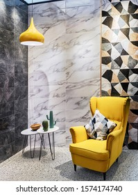 Yellow lamp and armchair in a modern interior in gray tones with porcelain stoneware walls