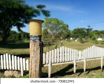 yellow lamp on old wooden pole and white  fence with backyard garden blurred background