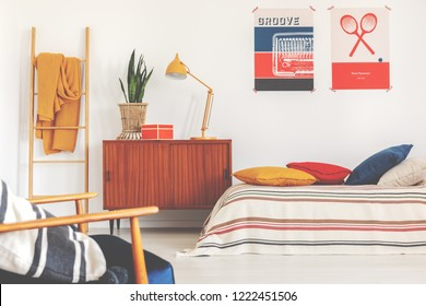 Yellow lamp and plant on wooden cabinet next to bed in sport bedroom interior with posters. Real photo